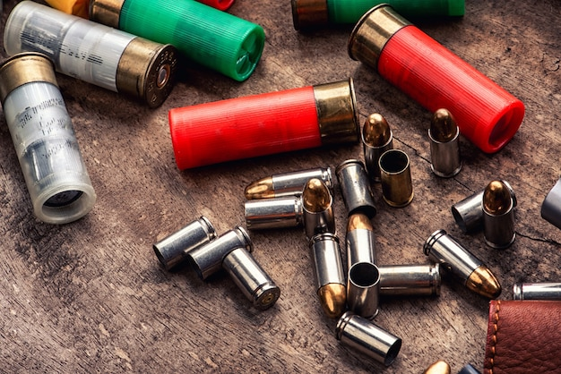 Pociski pistoletowe i magazynek porozrzucane na drewnianym stole