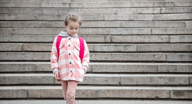 Początek lekcji i pierwszy dzień jesieni. słodka dziewczyna stojąca przed staris