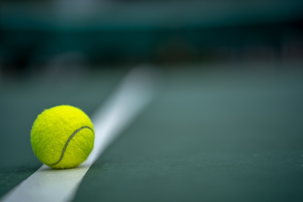 Początek mistrza, bliska piłka tenisowa na tle sądów.