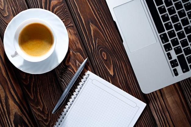 Początek porannej pracy biurka z filiżanką kawy komputer laptop, notatnik, długopis. drewniany stół tekstury. pomysł na biznes