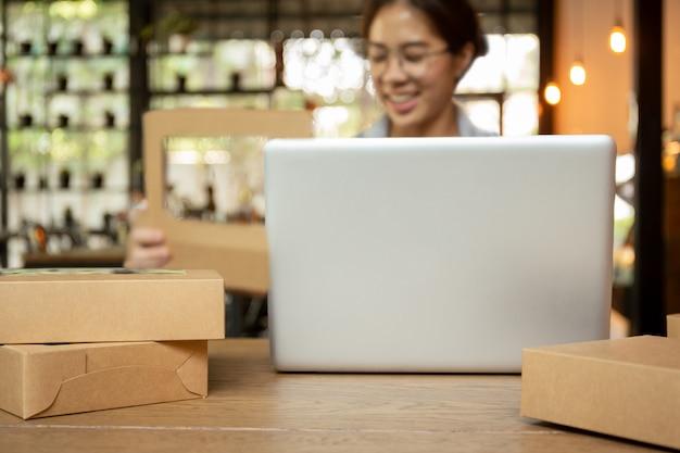 Początkowe biznesowe młode kobiety pracuje na laptopie z pakunkiem na stole.