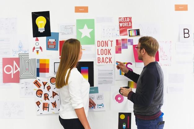 Początkowi ludzie biznesu patrzeje na tablicach informacyjnych informacje rozważnych