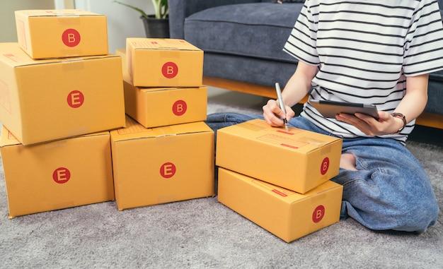 Początkowy mały biznes koncepcja, właściciel młodej kobiety pracuje i pakuje na pudełku do klienta przy kanapie w domowym biurze, sprzedawca przygotowuje dostawę.