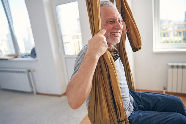Początkujący jogin ze szczęśliwym uśmiechem bujający się w hamaku na zajęciach aerial jogi