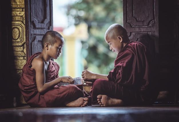 Początkujący mnich studiuje w świątyni czytając książkę, shan state temple w myanmarze