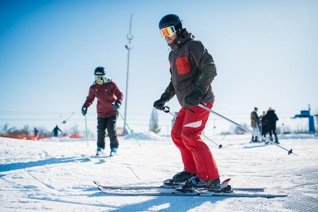 Początkujący uczą się jeździć na nartach, narciarze w sprzęcie, aktywny sport zimowy. narciarstwo z gór, ekstremalny styl życia