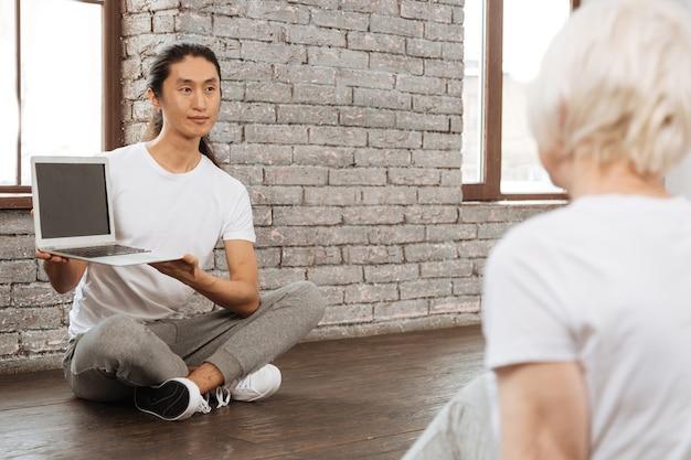 Poczekaj chwilę. pozytywny azjatycki mężczyzna krzyżuje nogi, siedząc na drewnianej podłodze, trzymając laptopa w obu rękach