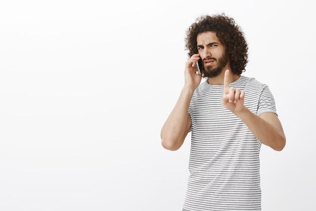 Poczekaj, to ważne połączenie. bossy męski atrakcyjny mężczyzna z brodą i fryzurą afro, pokazujący palec wskazujący w uciszeniu lub przytrzymaniu gestu