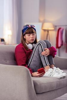 Poczekaj. uważna dziewczyna patrzy na swój gadżet i czeka na wiadomość