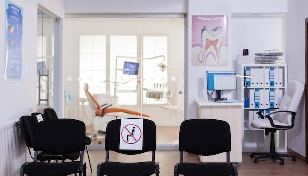 Poczekalnia w klinice bez nikogo w niej, recepcja z nową normalną mającą znak na krześle na odległość społeczną w pandemii koronawirusa