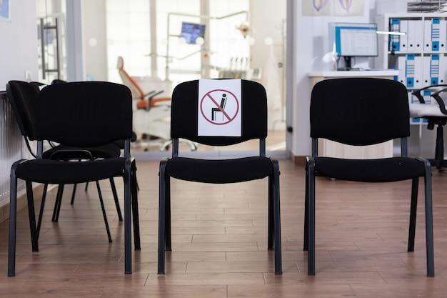 Poczekalnia w klinice, w której nikogo nie ma, recepcja z nową normalną, która ma znak na krześle na odległość społeczną w pandemii koronawirusa. pusty odbiór stomatologiczny podczas epidemii covid-19.