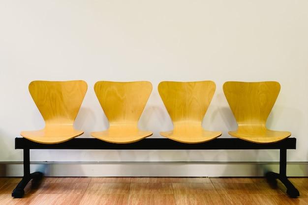 Poczekalnia z puste drewniane krzesła, koncepcja oczekiwania i upływ czasu, wolna przestrzeń dla tekstu.