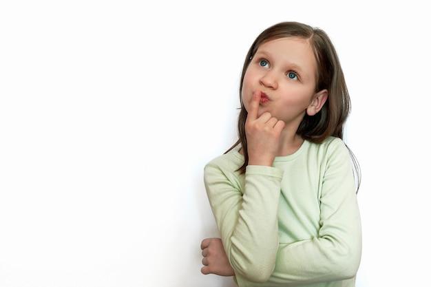 Poczęta dziewczyna na białym szarym tle trzyma palec wskazujący przy ustach