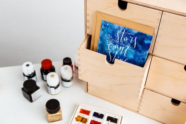 Pocztówka akwarela maluje tuszem na białym stole.