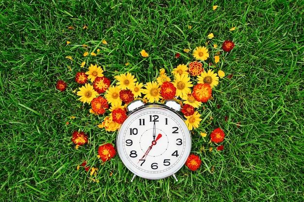 Pocztówka dzień dobry i budzik z żółtymi i czerwonymi kwiatami leżą na zielonej trawie