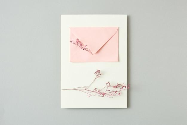 Pocztówka gratulacyjna z naturalnych gałęzi delikatnych kwiatów i papierowej różowej koperty na wiadomość na jasnoszarym tle, kopia przestrzeń. leżał płasko.