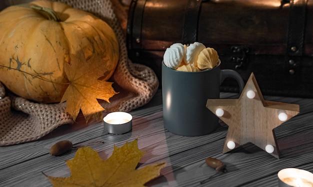 Pocztówka halloweenowe słodycze w kubku na ciemnym tle, dynia i płonąca gwiazda.
