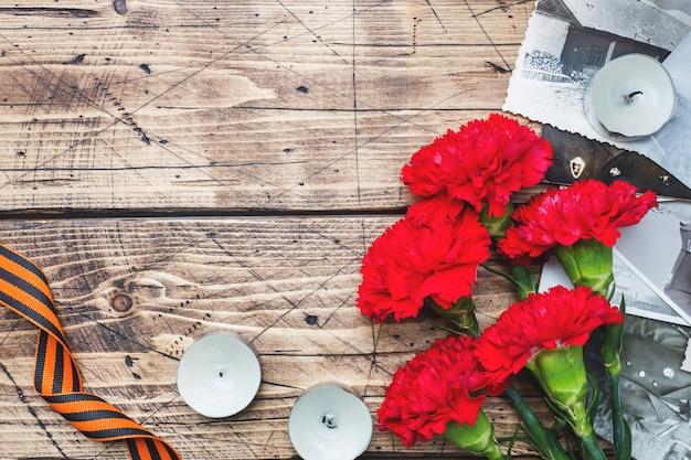 Pocztówka może 9 - czerwone goździki ribbon george stare zdjęcia na drewnianym tle.