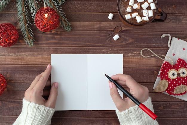 Pocztówka, prezent, kobiece dłonie, świąteczne dekoracje i kakao