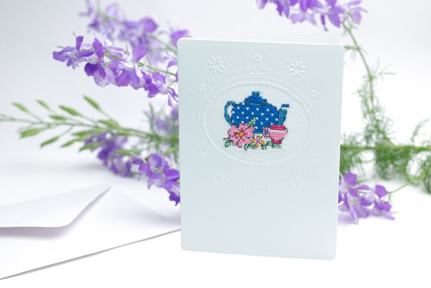 Pocztówka z haftem czajnik na tle fioletowych kwiatów consolida regalis