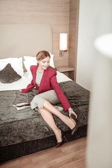 Poczuć ulgę. blondynka, odnosząca sukcesy bizneswoman, odczuwa ulgę podczas zdejmowania butów