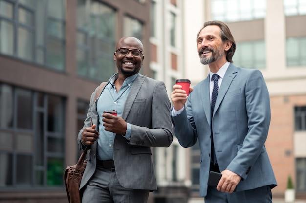 Poczucie motywacji. wesołych biznesmenów pijących kawę rano zmotywowani