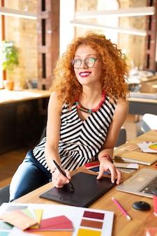 Poczucie prawdziwej inspiracji. stylowa kobieta w okularach czuje się naprawdę zainspirowana o poranku