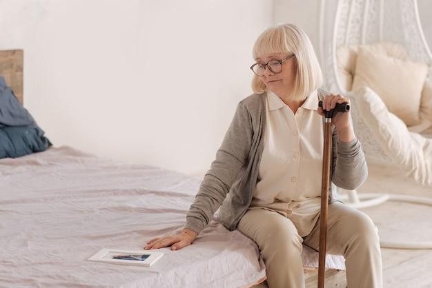 Poczucie samotności. posępna, przygnębiona starsza kobieta trzymająca laskę i patrząc na zdjęcie swojego męża, siedząc na łóżku