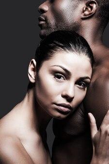 Poczucie spokoju i ochrony. piękna kobieta rasy kaukaskiej przywiązująca się do pleców przystojnego afrykańskiego mężczyzny i patrząca w kamerę, stojąc na szarym tle
