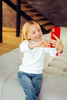 Poczucie szczęścia. wesoły dzieciak z uśmiechem na twarzy podczas pozowania przed kamerą