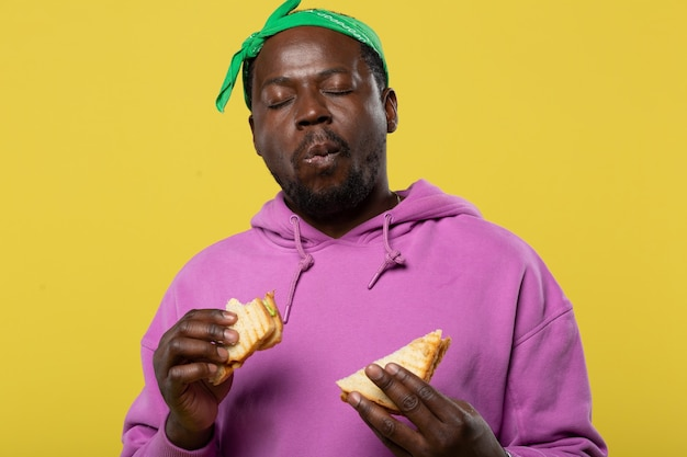 Poczuj chwilę. miły ciemnoskóry mężczyzna trzymający chleb w obu rękach, delektując się jedzeniem