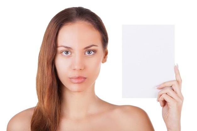 Poczuj różnicę. portret pięknej młodej kobiety z pół makijażem twarzy trzymającej miejsce na kopię i patrzącej na kamerę, stojąc na białym tle na białym tle