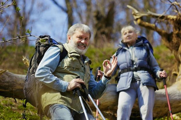 Poczuj się dobrze i ciesz się. starsza rodzina para mężczyzna i kobieta w strój turystyczny spaceru na zielonym trawniku w pobliżu drzew w słoneczny dzień. pojęcie turystyki, zdrowego stylu życia, relaksu i wspólnoty.