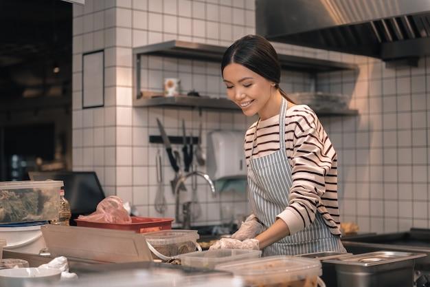 Poczuj się radośnie. ciemnowłosa właścicielka restauracji radośnie pracuje na własną rękę w kuchni