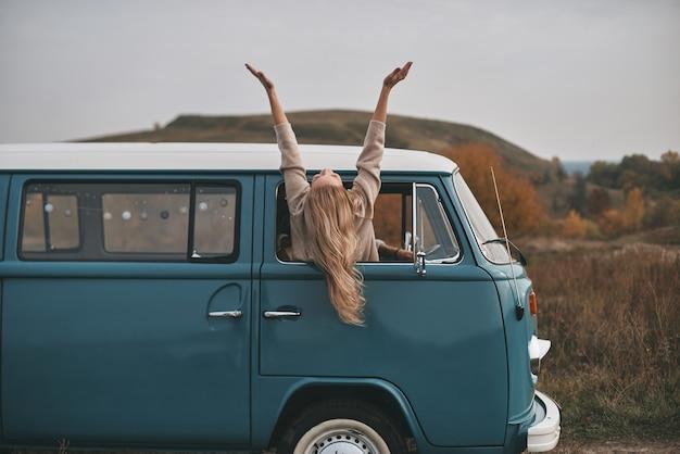 Poczuj Swoją Wolność! Atrakcyjna Młoda Kobieta Wychylająca Się Przez Okno Furgonetki I Trzymająca Wyciągnięte Ręce, Ciesząc Się Podróżą Samochodem Premium Zdjęcia