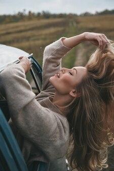 Poczuj wiatr we włosach! atrakcyjna młoda uśmiechnięta kobieta wychylająca się przez okno furgonetki i trzymająca rękę we włosach, ciesząc się podróżą samochodem