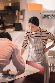 Poczuj złość. ciemnowłosa właścicielka restauracji czuje złość po sprawdzeniu pracy kelnera