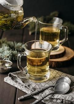 Pod dużym kątem, ręcznie nalewanie herbaty w szklance z czajniczkiem
