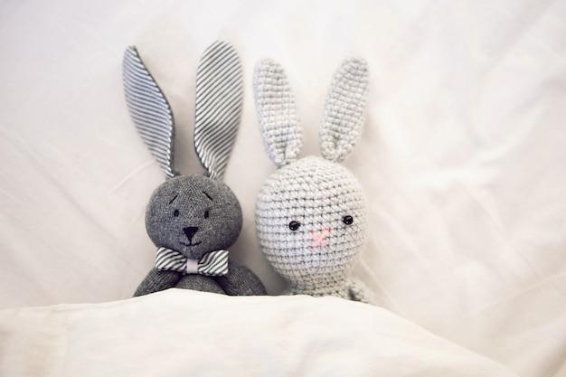 Pod kocem na białym łóżku leżą dwie robione na drutach zabawki z królikami