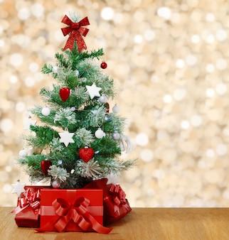Pod ozdobną choinką znajdują się czerwone pudełka z prezentami.