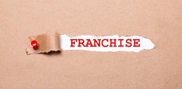 Pod podartym paskiem papieru pakowego z czerwonym guzikiem znajduje się biały papier z napisem franchise