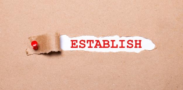 Pod rozdartym paskiem papieru pakowego przymocowanym czerwonym guzikiem znajduje się biały papier establish