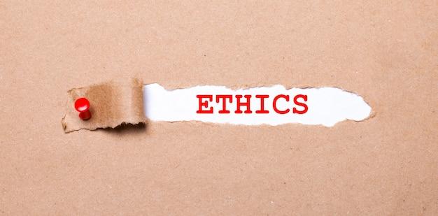 Pod rozdartym paskiem papieru pakowego z czerwonym guzikiem znajduje się biały papier z napisem etyka