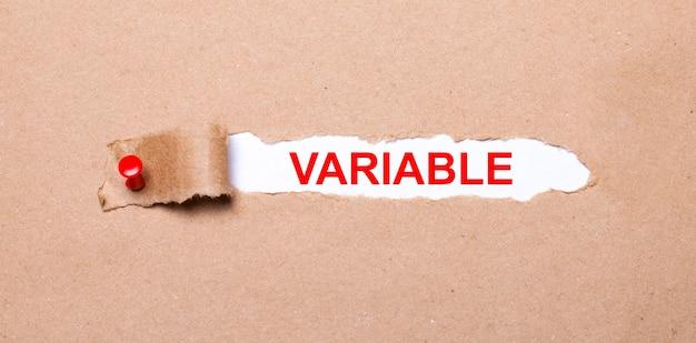 Pod rozdartym paskiem papieru pakowego z czerwonym guzikiem znajduje się biały papier z napisem variable