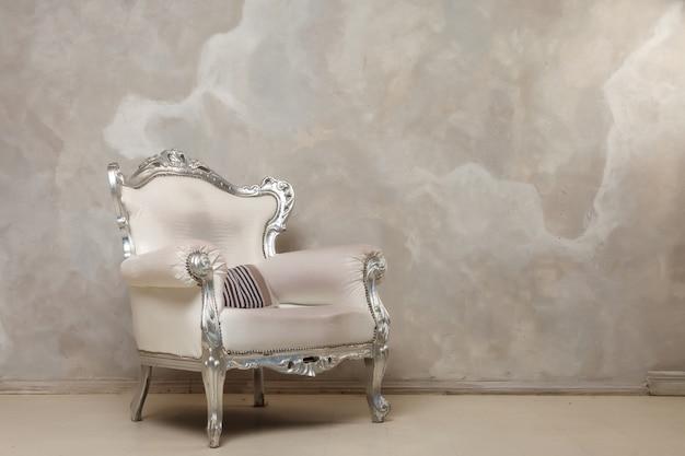 Pod ścianą stoi antyczne białe krzesło