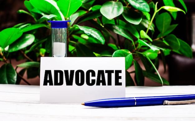 Pod ścianą zielonych liści rośliny na stole długopis, klepsydra i kartka z napisem advocate