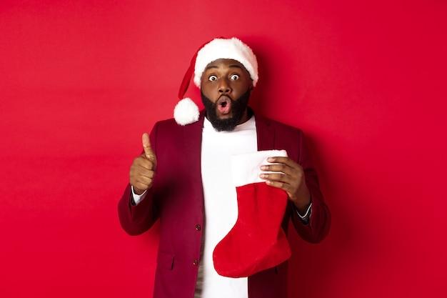 Pod wrażeniem afroamerykanin trzyma skarpetę świąteczną