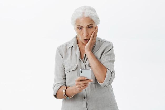 Pod wrażeniem babci patrzy na ekran smartfona ze zdumieniem