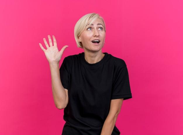 Pod wrażeniem blond kobieta w średnim wieku, patrząc na bok, robi gest hi na białym tle na różowej ścianie