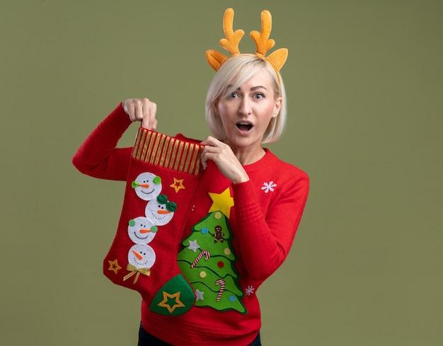 Pod wrażeniem blond kobieta w średnim wieku ubrana w opaskę z poroża renifera i świąteczny sweter trzyma świąteczną skarpetę, patrząc na kamerę odizolowaną na oliwkowym tle